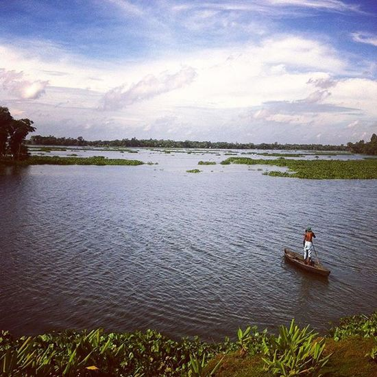 A man with his boat crossing a water body in a remote village. Js Jashimsalam Photographer Photojournalist Photojaournalism Documentary Dailylife Whpfilltheframe Landscape Autumnfs Nature Natgeo Man Boat Water Horizon Sky Cloud Village Photo Photos Bangladesh Instagram Everydaybangladesh