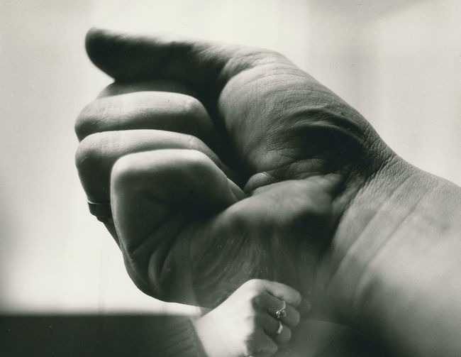 Cropped hands of man and woman clenching fist
