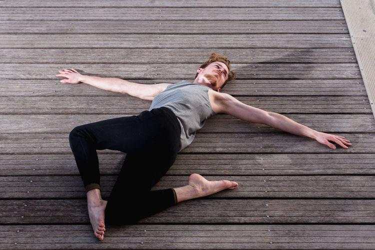 Full length of man lying on wooden floor