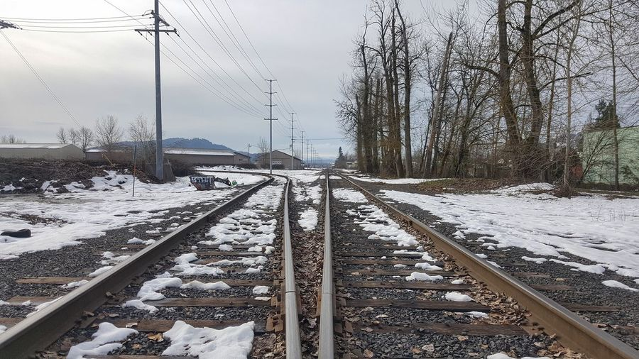 Snow covered railroad tracks against sky during winter