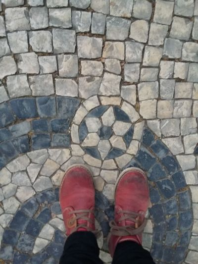 Portuguese cobblestone sidewalk. Lisbon-Portugal. Floortraits Floortrait Coblestone Street Portuguese Cobblestone Shoe Low Section High Angle View Standing Personal Perspective Human Leg Real People One Person Directly Above Human Body Part Lifestyles
