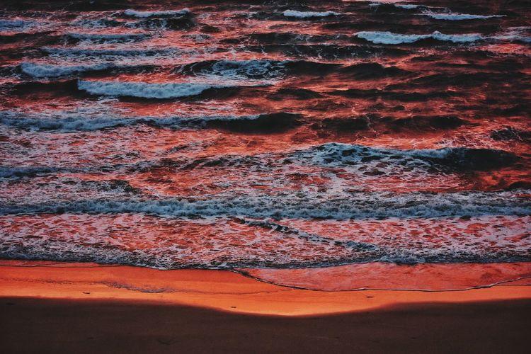 Atlantic ocean waves in red sunrise light on fuerteventura canary island in spain