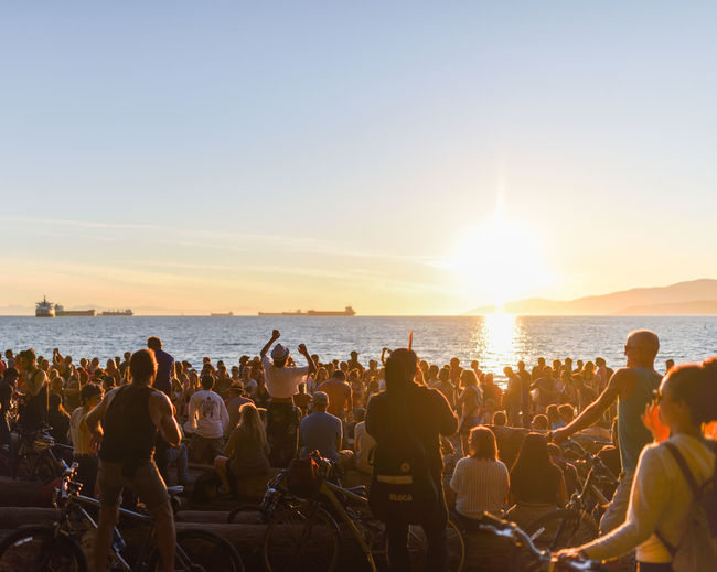People at beach against clear sky during sunset