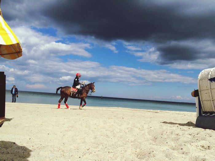 Jockey Riding Horse On Beach Against Sky