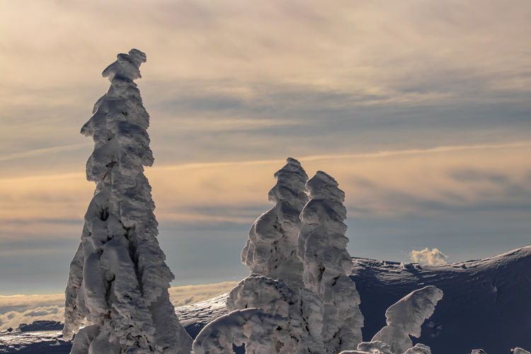 Rock formation on snow against sky during sunset