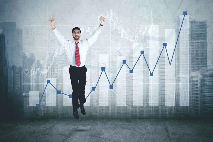 Digital Composite Image Of Businessman With Arms Raised Jumping Against Chart