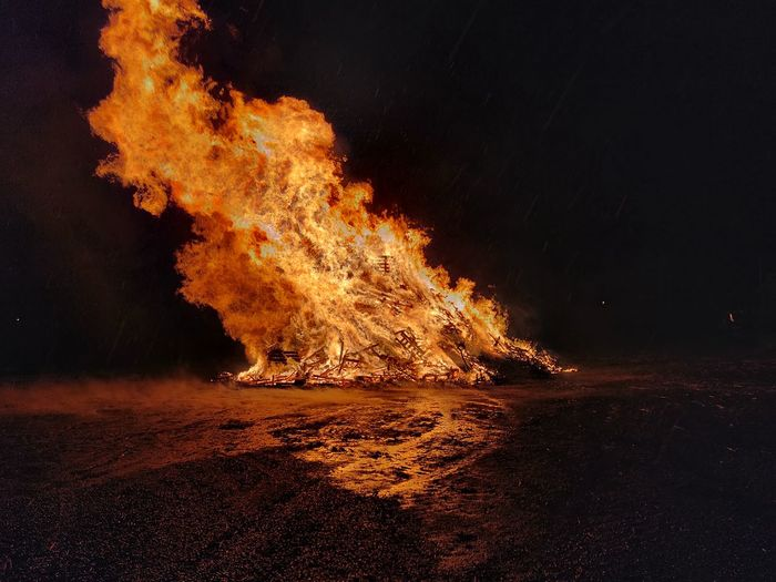 Panoramic view of bonfire on beach at night