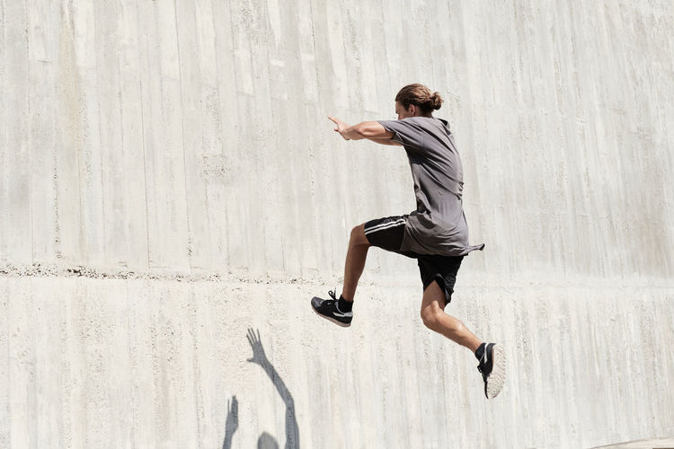 Side view of young man jumping against wall