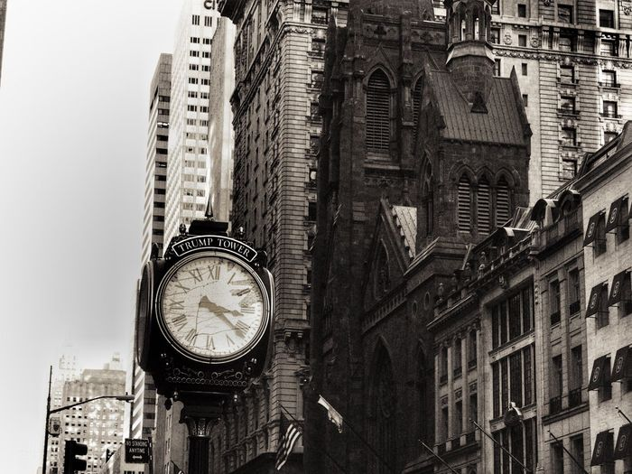 Low angle view of clock by buildings in city