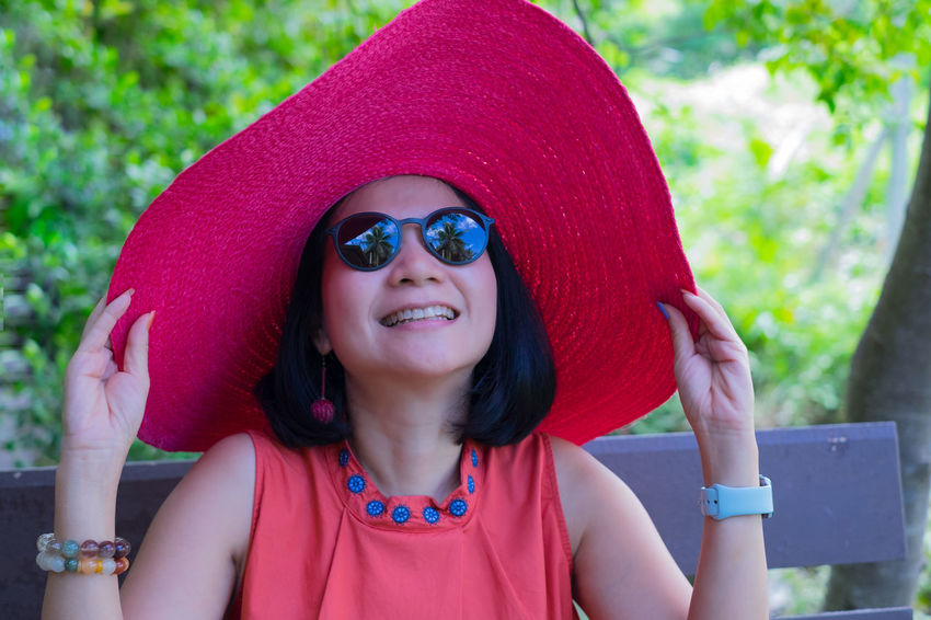 Front View One Person Lifestyles Portrait Headshot Leisure Activity Smiling Red Happiness Focus On Foreground Day Hat Fashion Emotion Vacations Sunglasses Greenery Summer Casual Clothing Holding Happiness Joyful Park Garden Springtime