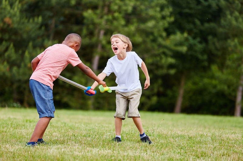 Boys playing with toy swords at park