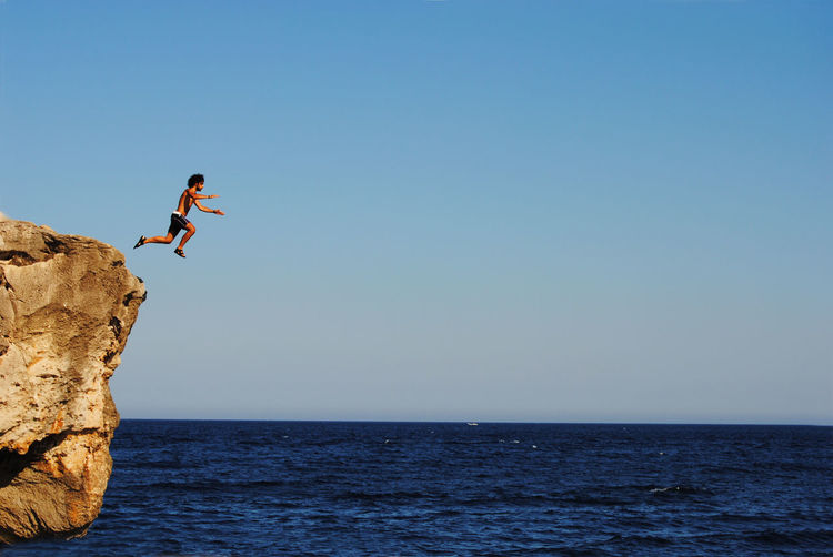 Full length of shirtless man jumping from cliff into sea