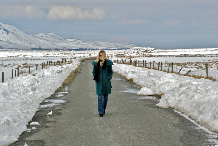 Woman walking on road during winter