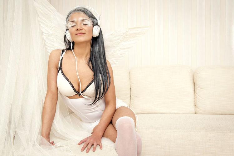 Female Model In Angel Costume Wearing Headphones While Sitting On Sofa