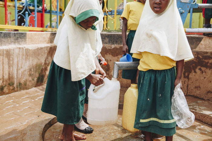 Africa African Barefoot Carrying Child Children Dirt Dirty Drinking Water Filling Girls Health Muslim Outdoors PLASTIC CONTAINER Pump Real People School Students Uniform Unsafe Water Water Pump Well  Yard