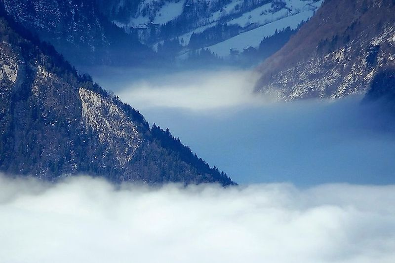 Different shades of grey fog floating into the side-valleys in Kanton Uri in the Central Swiss Alps Beauty In Nature Blue Cloud - Sky Day Dreamlike Fog Geology Idyllic Majestic Mountain Mountain Peak Mountain Range Nature No People Outdoors Remote Scenics Shades Of Grey Sky Swiss Alps Switzerland Tranquility Uri Valley