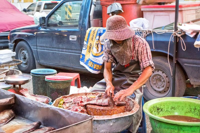 Man Cutting Fish For Sale At Market