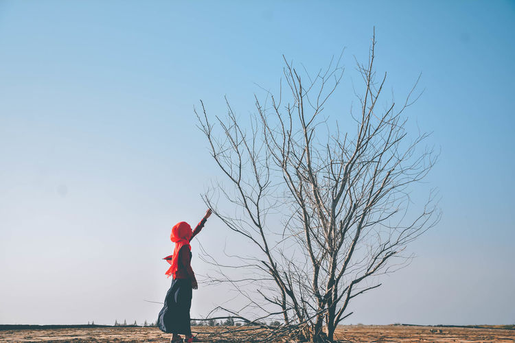 Drought. Sky Real People One Person Standing Land Side View Lifestyles Tree Nature Field Day Child Arid Landscape Arid Climate Muslimah Beauty In Nature Dry Tree Childhood Scenics - Nature Backgrounds