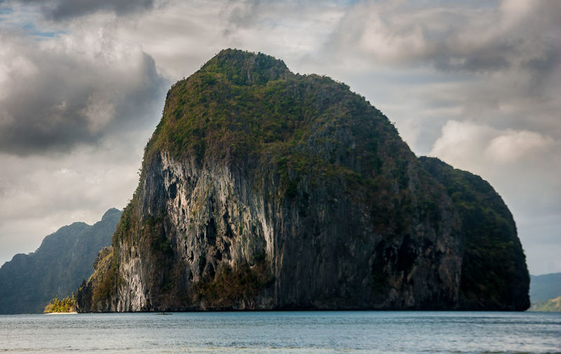 Scenic View Of Rock Formation In Sea Against Cloudy Sky At El Nido