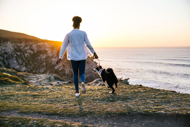 Rear view of woman with dog on street during sunset