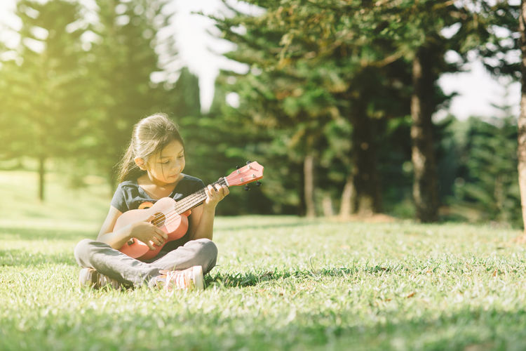 Girl playing guitar on field against trees
