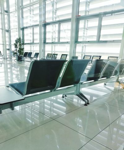 Empty airport waiting room at gate departure Travel Destinations Travel Departure Waiting For Take Off Typical Nobody Empty Sunny Glass - Material Gate Tranquil Scene Destination Seat Technology Industry Computer Business Finance And Industry Factory Innovation Airport Architecture Built Structure Airport Departure Area Passenger Boarding Bridge Transportation Building - Type Of Building Airport Terminal Transparent Glass - Material Airport Runway