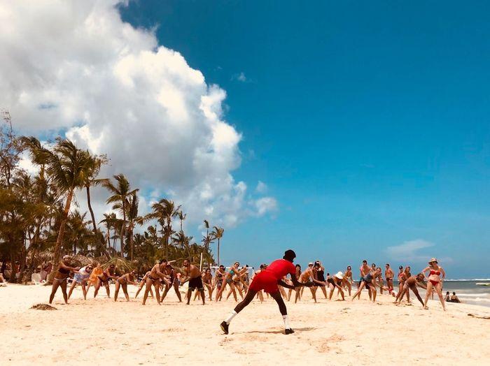 People Dancing At Beach Against Sky