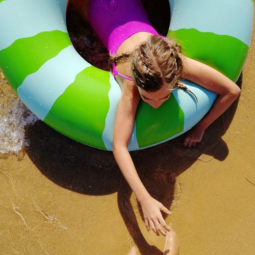 High angle view of girl relaxing on inflatable ring at beach