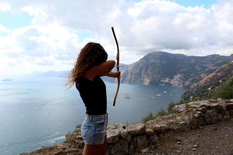 Side View Of Woman Practicing Archery On Cliff Against Sea