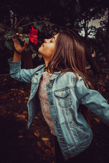 Girl smelling flower growing on plant at park