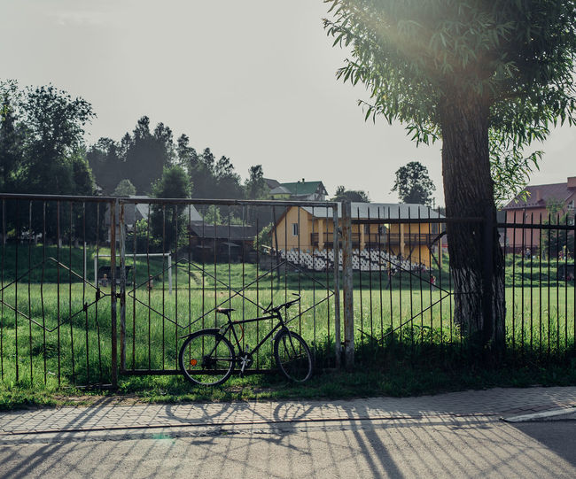 Bicycle by house against sky