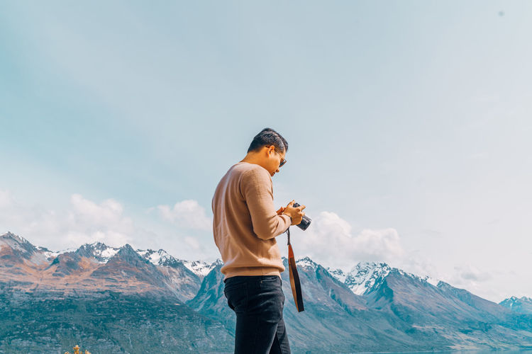 Man holding camera while standing on land against mountains and sky