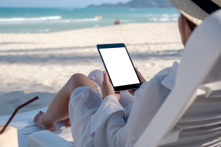 Mockup image of a woman holding a black tablet pc with blank desktop screen while laying down on beach chair on the beach Background Beach Black Blank Chair Communication Computer Connection Copy Copyspace Desktop Device Display Down Empty Female Girl Hand Holding Holiday Internet Laying Lifestyle Look Message Mock Mockup Nature Online  Outdoors Over PC People person Relax Sand Screen Sea Shoulder Space