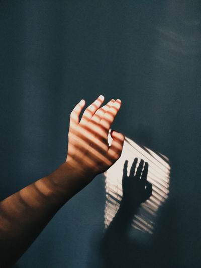 Cropped hand of woman with shadow against wall