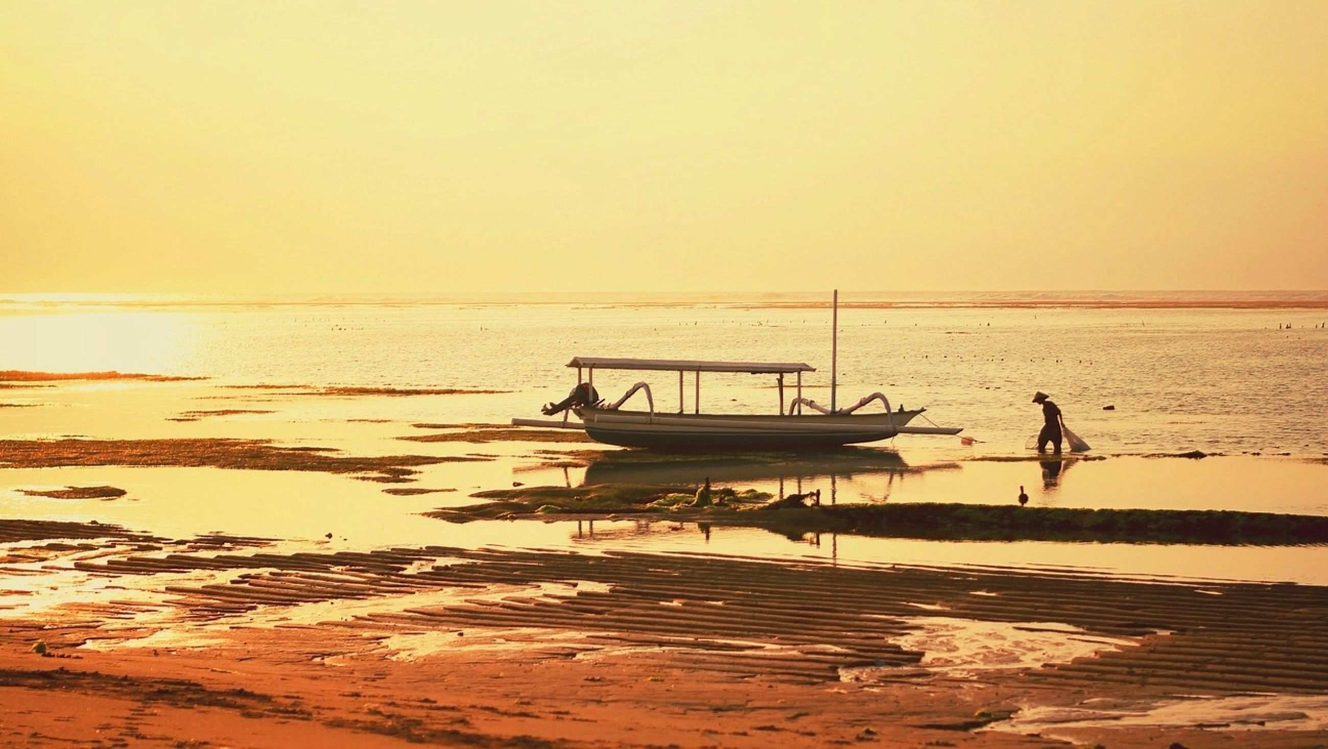 sea, water, sunset, horizon over water, beach, clear sky, tranquil scene, tranquility, scenics, beauty in nature, copy space, shore, nautical vessel, nature, transportation, orange color, boat, silhouette, idyllic, sand