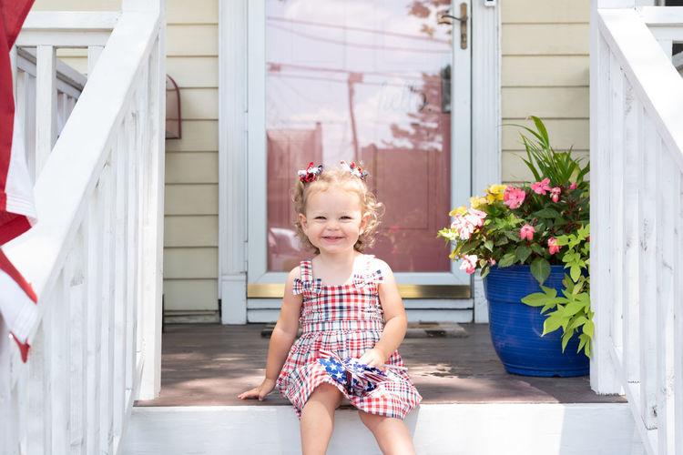 Full length of smiling girl sitting outdoors