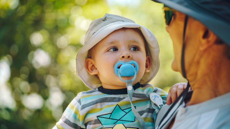 Close-up of baby boy with pacifier in mouth being carried by father