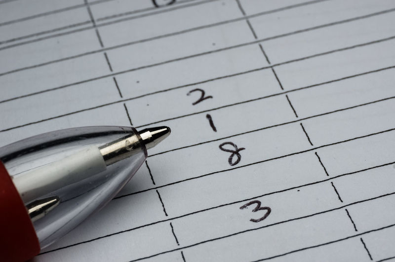 Close-Up Of Pen On Paper With Numbers