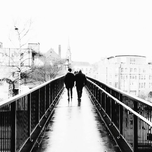 Walking to church Walking Two People Footbridge Bridge - Man Made Structure Railing Adults Only Architecture Blackandwhite Photography Church Tower Contrasts River Men Leisure Activity Real People Outdoors Day Only Men Adult Sky People Athlete Water Nature