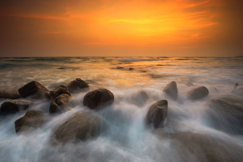 Beautiful natural seascape wave moving on the rock during sunrise,, Rayong Thailand Motion Water Sea Sky Scenics - Nature Rock Beauty In Nature Rock - Object Solid Sunset Long Exposure Horizon Over Water Horizon Cloud - Sky Nature Blurred Motion Beach Wave Land No People Outdoors Power In Nature Flowing Water Sunrise Rayong,Thailand 2018 In One Photograph