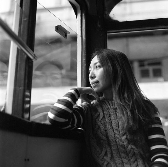 Young woman looking through window in bus
