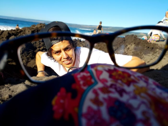 Portrait of young man seen through eyeglasses on rocky shore