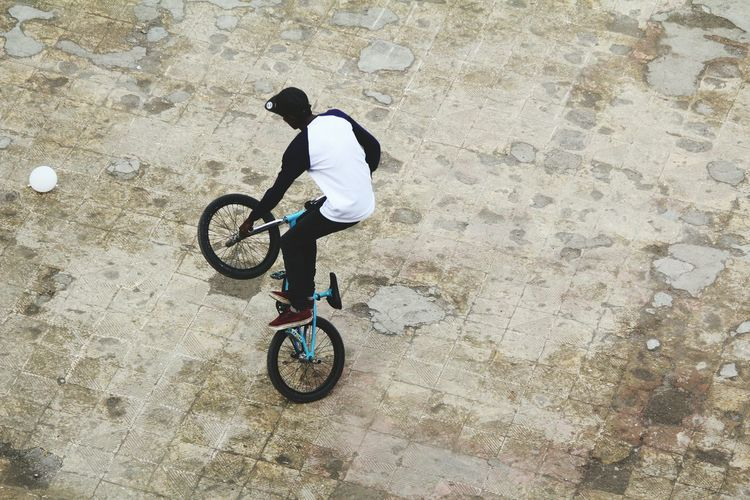 Man Performing Stunt With Bicycle On Footpath