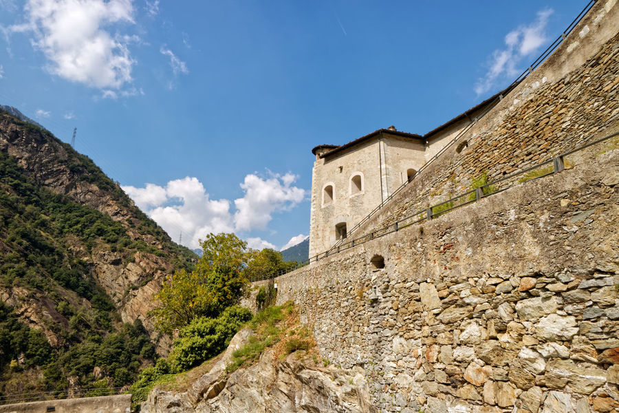 Fort Bard, Valle d'Aosta, Italy - Agoust 18, 2017: Historic military contruction defence Fort Bard. Touristic medieval fortress in Italian Alps. Location of the Avengers: Age of Ultron film. Ancient Avengers EyeEmNewHere Rock Romantic The Week On EyeEm Travel Trip Vacations Your Ticket To Europe Alps Architecture Building Exterior Built Structure Castle Cloud - Sky Day Destination Editorial  Famous Places Historic History Italy Location Low Angle View Mountain Mountains Nature No People Old Buildings Outdoors Sky Tourism Travel Destinations Tree Wall - Building Feature