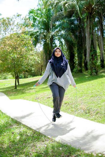Full length of woman on footpath in park