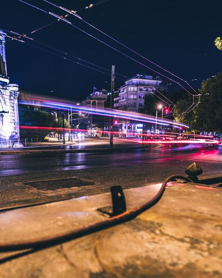 Light trails on street against illuminated city at night