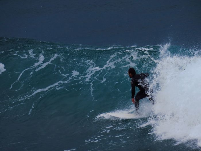 Man surfboarding in sea against sky