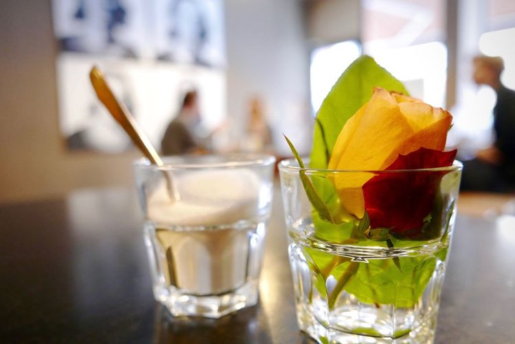 Close-Up Of Rose And Food In Glasses On Table At Coffee Shop