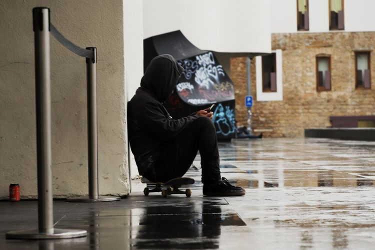 Side view of man sitting in rain