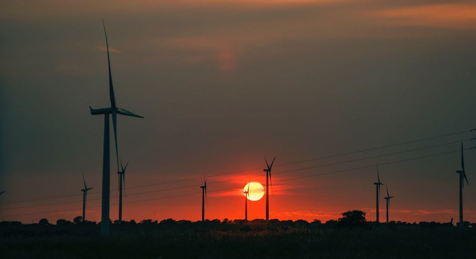 Silhouette of wind turbines on field against sky during sunset